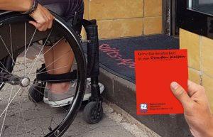 Rollstuhlnutzerin vor Stufe an einer Apotheke mit Roter Karte
