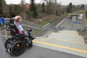 Uwe Frevert mit E-Rolli vor vielen Stufen zum Bahnsteig