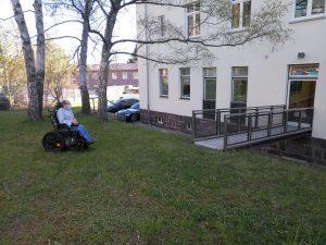 Uwe Frevert mit E-Rollstuhl auf Wiese vor Rampe zur Zahnarztpraxis